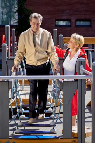 Kaksi ikäihmistä harjoittelee liikuntalaitteessa.