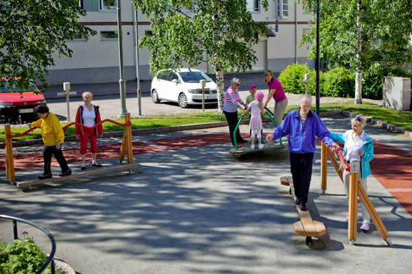 Ikäihmisiä treenaamassa liikuntapuiston laitteissa.